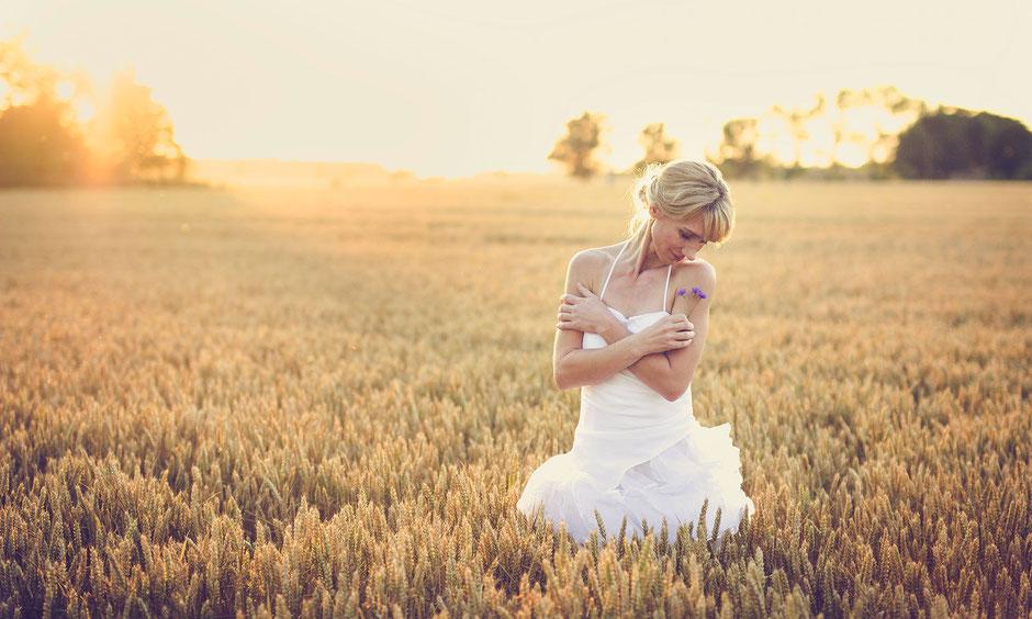 Frau im weißen Kleid beim Fotoshooting im Getreidefeld