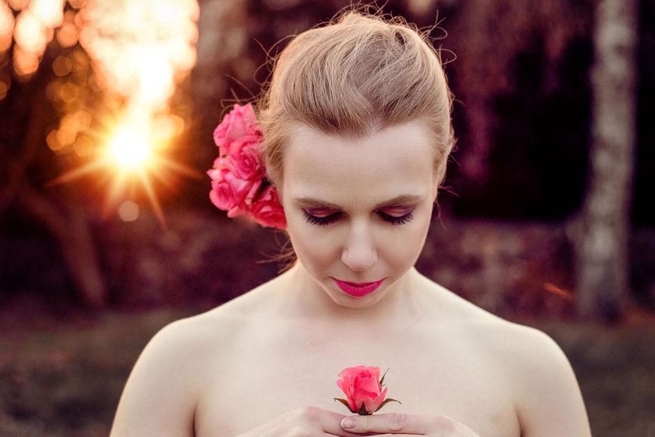 Portrait einer Frau im Sonnenuntergang mit pinken Rosen