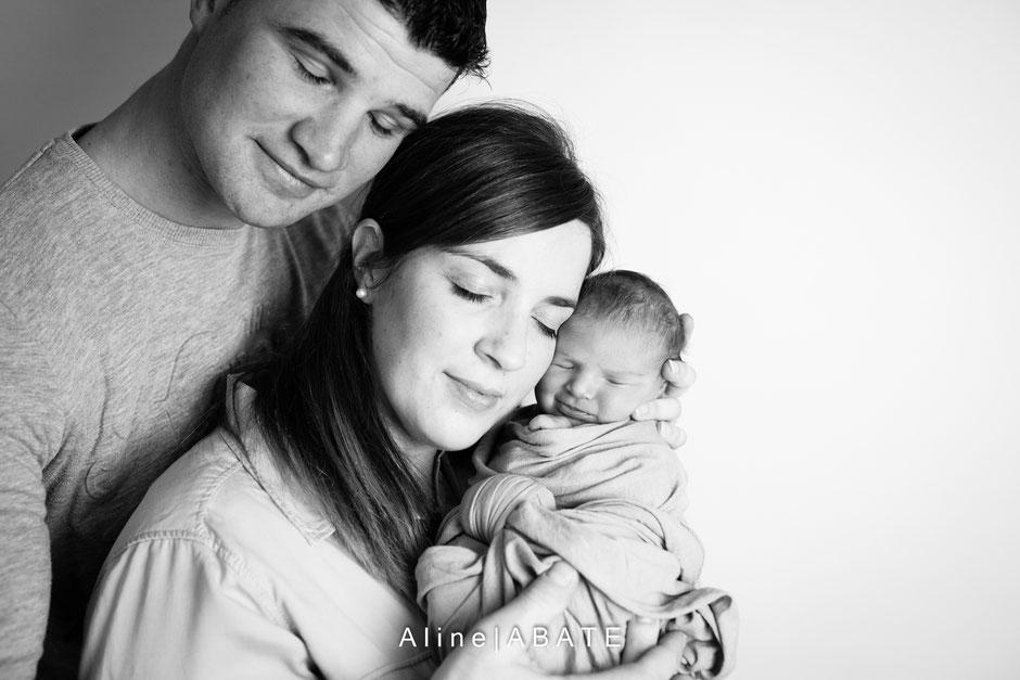 photo en noir et blanc de nouveau né emmailloté avec les parents