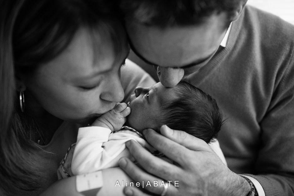 Photo de nouveau né avec ses parents l'embrassant