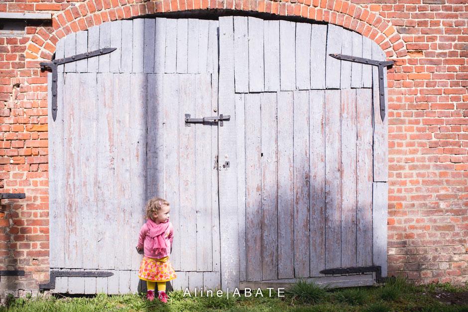 enfant adossé à une porte de garage bleue
