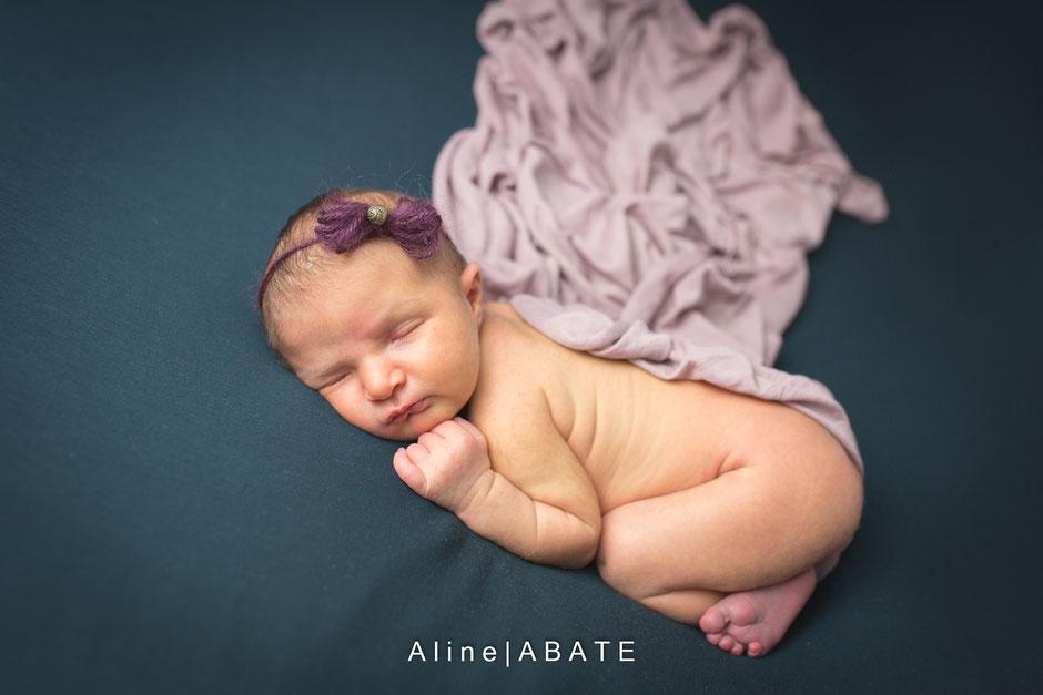 photo de nouveau né en studio sur une couverture verte et accessoires prune