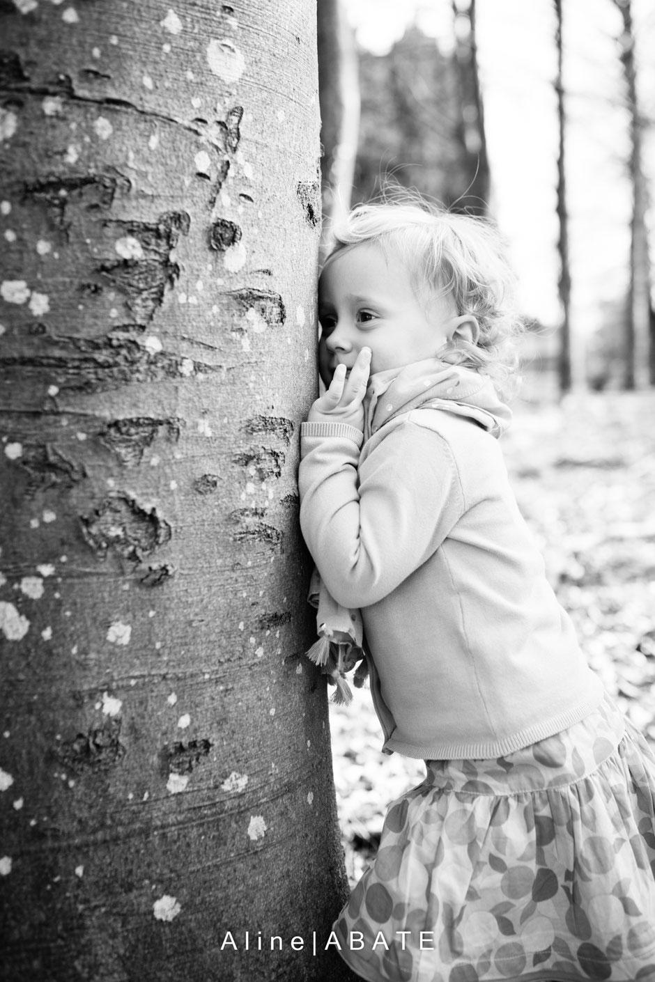 enfant jouant à cache-cache derrière un arbre