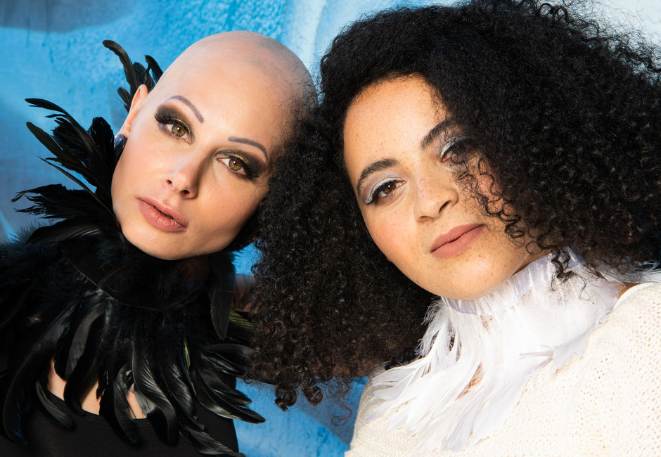 Diversity - zwei sehr unterschiedliche Frauen gemeinsam auf einem Bild. Eine mit Glatze, die andere mit sehr vielen Locken - beide schön.