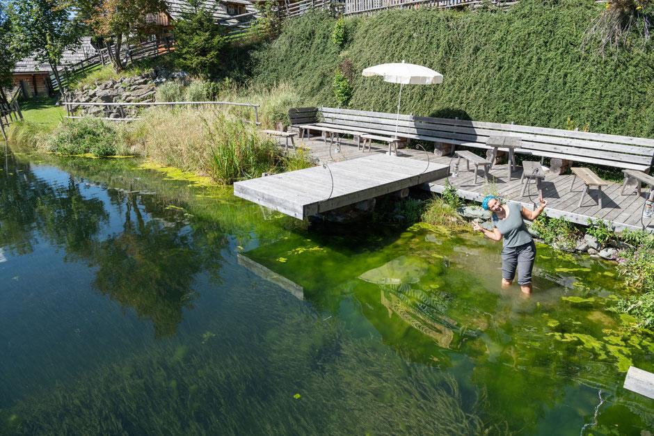 """Fotografin steht im Teich des Resorts """"Almdorf Seinerzeit"""" in Kärnten, auf der Suche nach einer guten Position, um die Outdoor - Hochzeit zu fotografieren."""