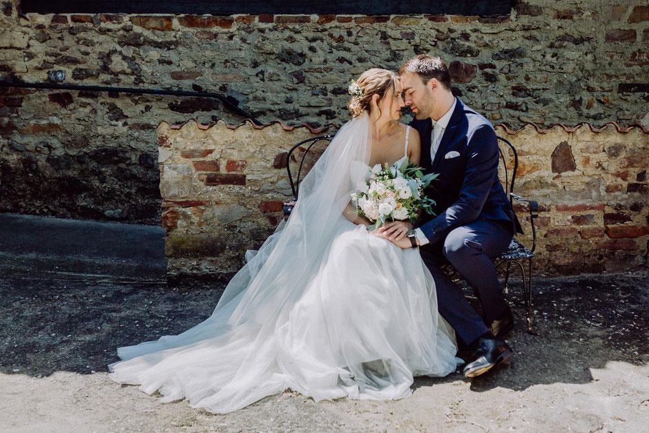 glückliches Brautpaar sitzt auf einer Bank auf Schlossgut Diel bei Bad Kreuznach