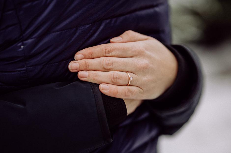 Nahaufnahme einer Frauenhand mit rosegoldenem Verlobungsring mit Diamant