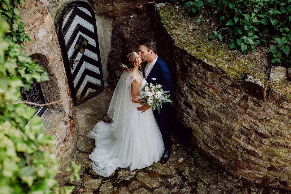 Brautpaar küsst sich im Burghof bei Brautpaar-Fotoshooting auf Burg Layen bei Bad Kreuznach