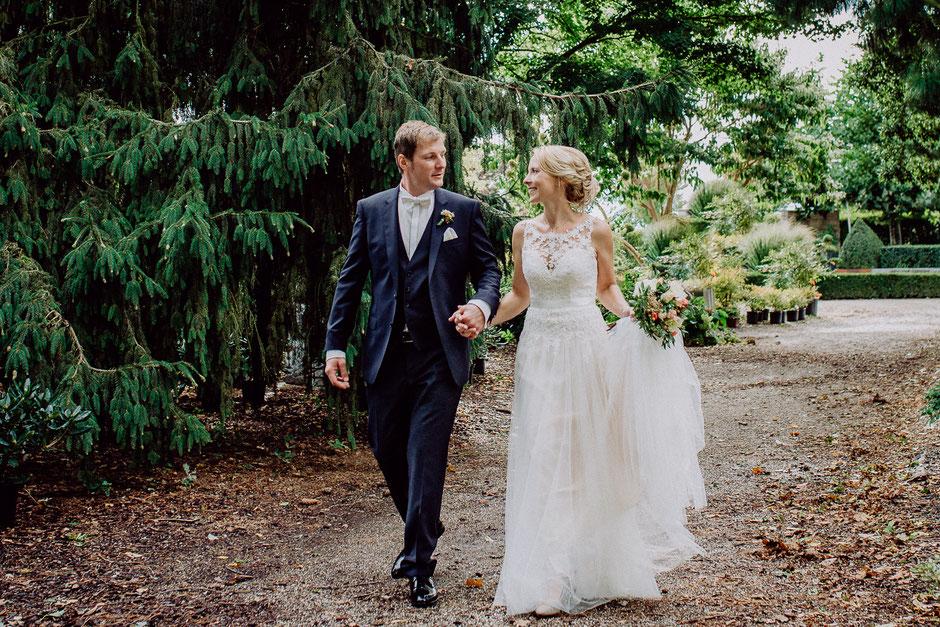 Brautpaar geht bei Brautpaarshooting in Baumschule Huben in Ladenburg spazieren