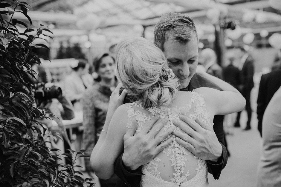 Braut umarmt Schwager bei Gratulationen in Hochzeitslocation Gewächshaus in Mannheim