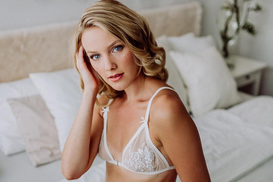 junge Braut sitzt in schöner Wäsche auf dem Bett bei sinnlichem Fotoshooting in Mainz