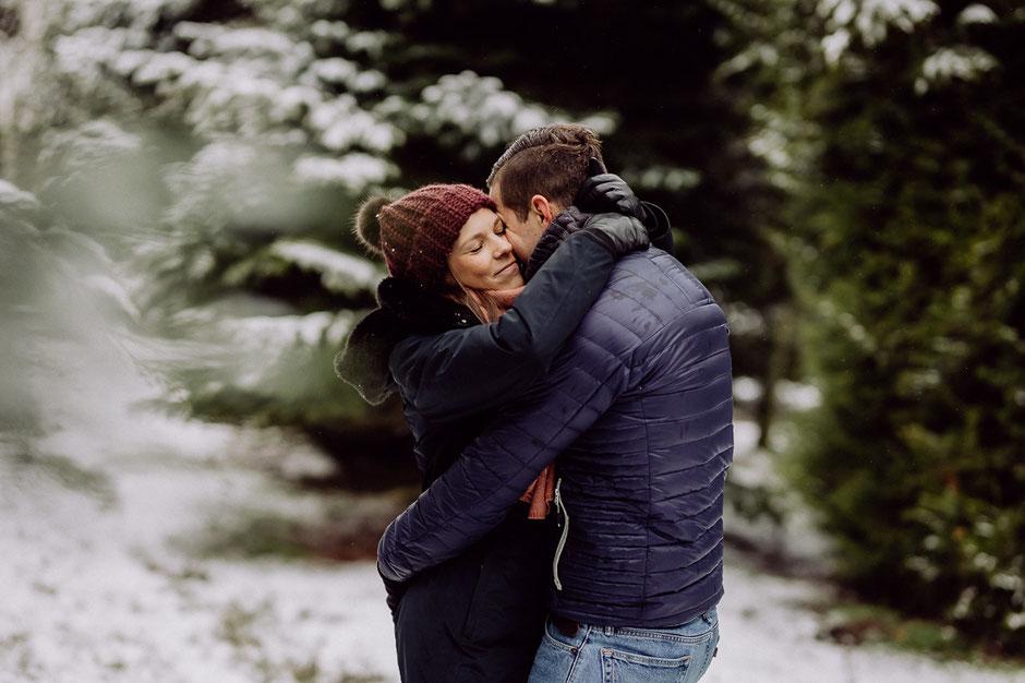 Paar umarmt sich und steht im Schnee im Wald in Rheinland-Pfalz