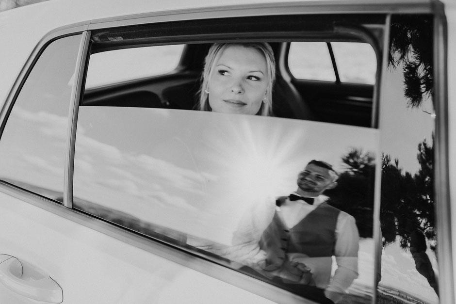 Braut im Brautauto schaut Bräutigam an, der sich im Fenster spiegelt