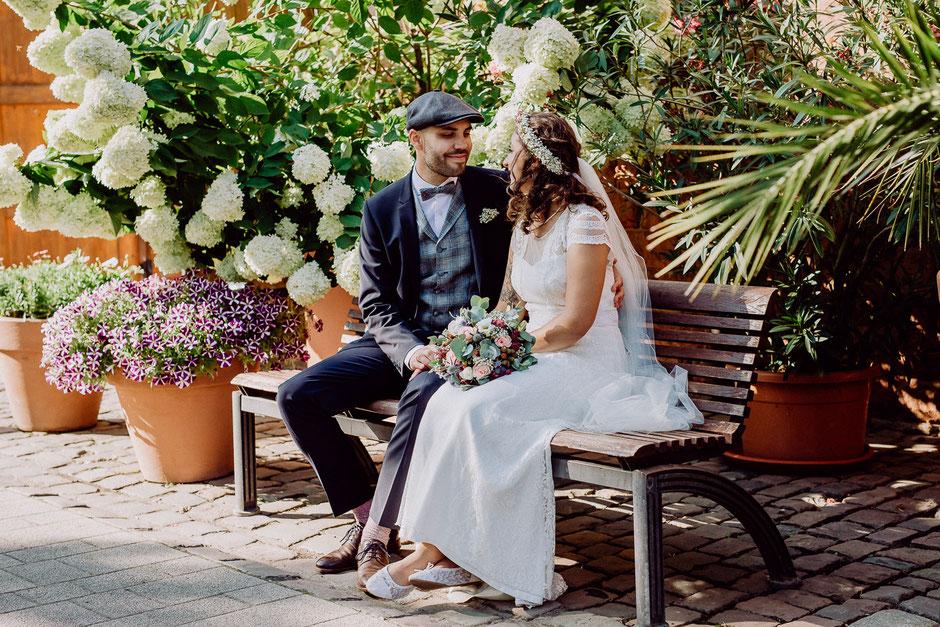 Braut und Bräutigam sitzen auf einer Bank