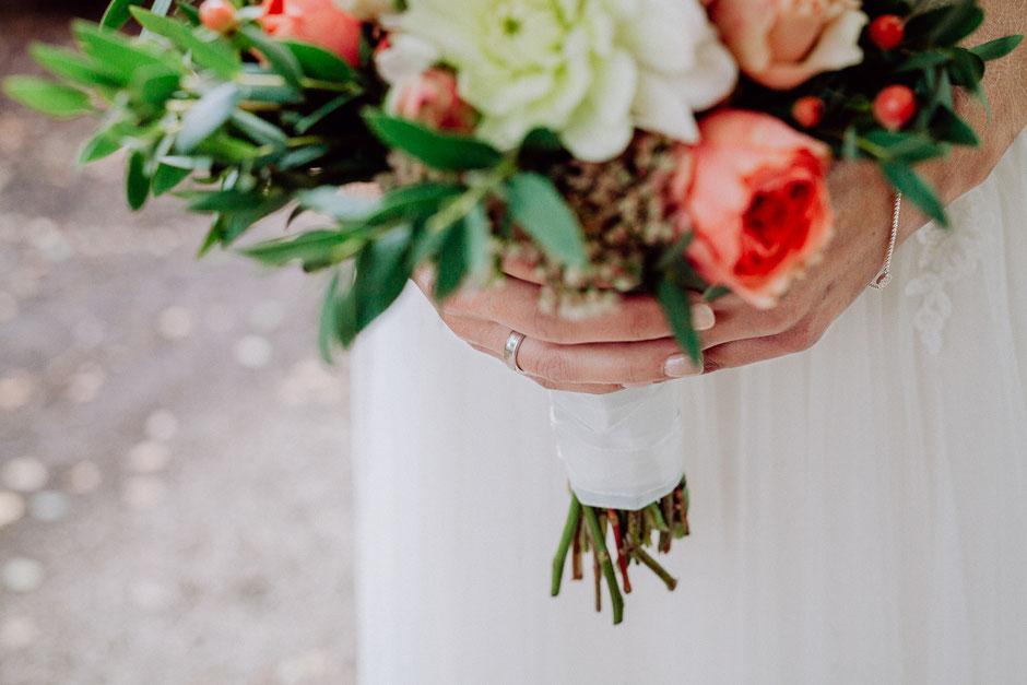 Detailaufnahme des Eheringes an der Hand der Braut mit Brautstrauss