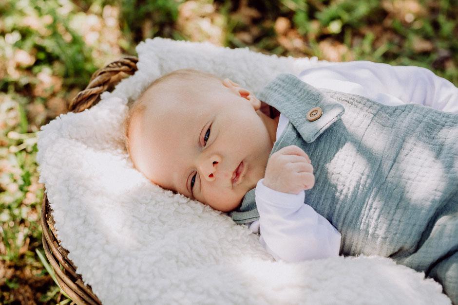 Säugling liegt mit geöffneten Augen im Korb bei Fotoshooting in Bodenheim