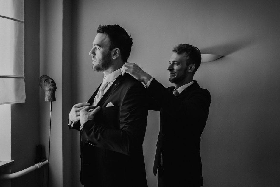 Trauzeuge hilft Bräutigam beim Anziehen des Jacketts vor der freien Trauung in Bad Kreuznach