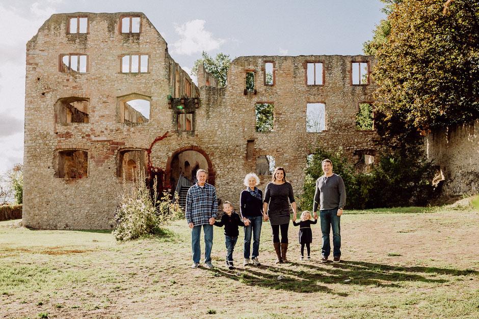 Familie steht mit Kindern und Großeltern vor Burgruine in Rheinhessen