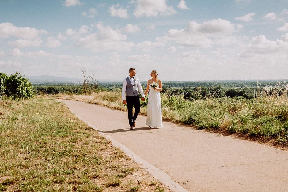 Brautpaar geht Hand in Hand auf einem Weg in den Weinbergen bei Mainz