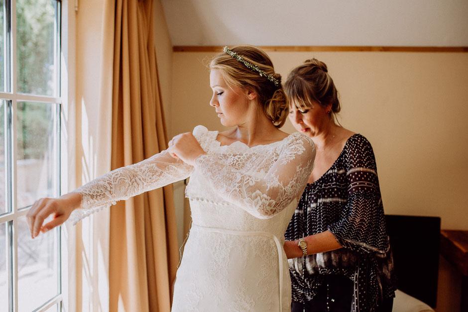 Braut zieht Brautkleid mit langen Ärmeln an