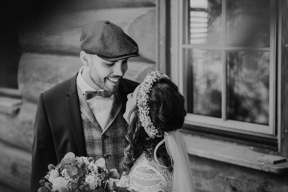 ein glückliches Brautpaar lächelt sich an