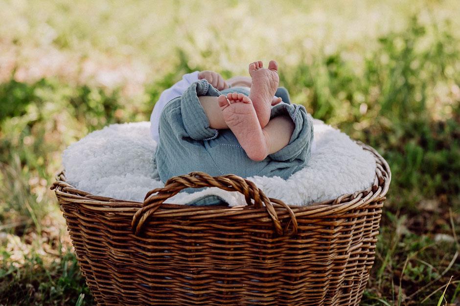 Baby liegt im Weidenkorb auf einer Wiese und streckt die Füße hin