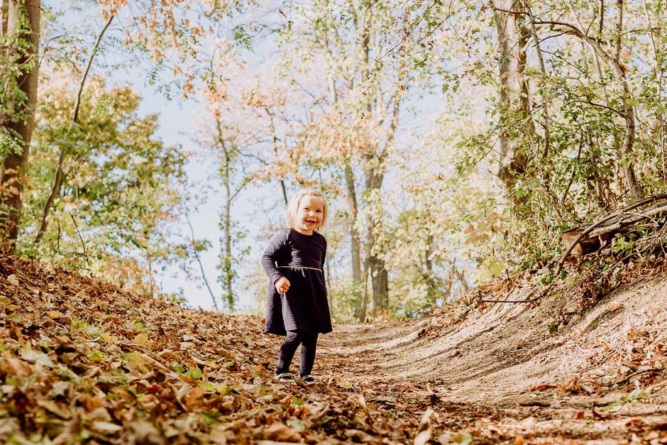Kleines Mädchen steht lachend im Wald im Herbst