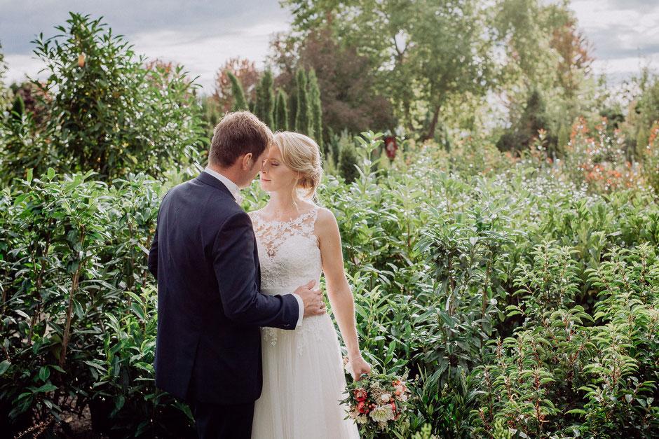 Brautpaar im Garten im Gegenlicht in romantischer Pose bei Brautpaarshooting in Ladenburg
