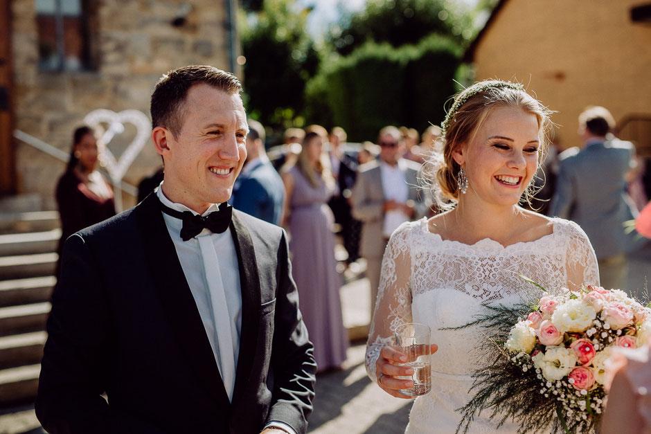 fröhlich lächelndes Brautpaar