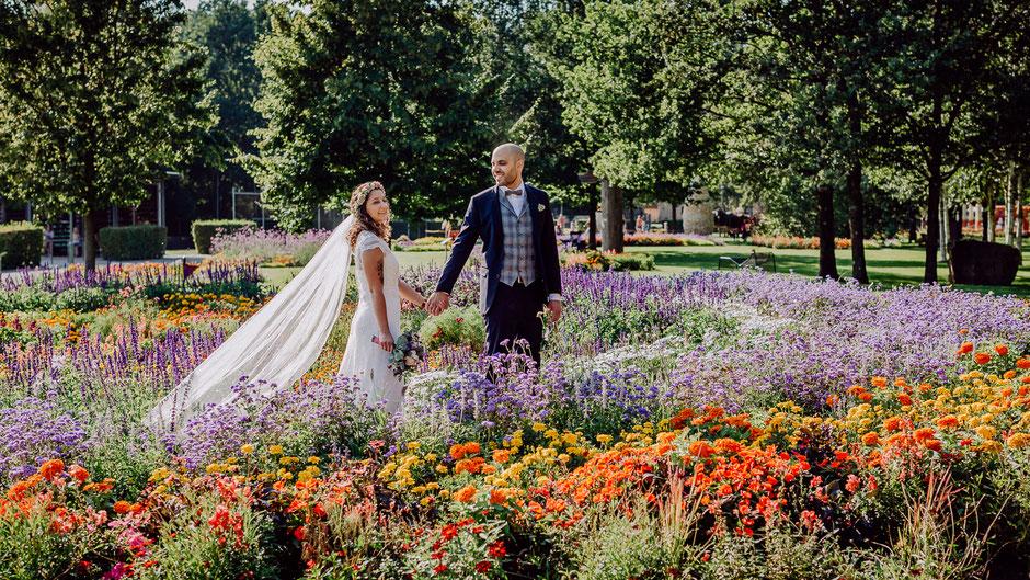 Braut und Bräutigam gehen Hand in Hand durch ein Blumenmeer bei Hochzeit in Kaiserslautern