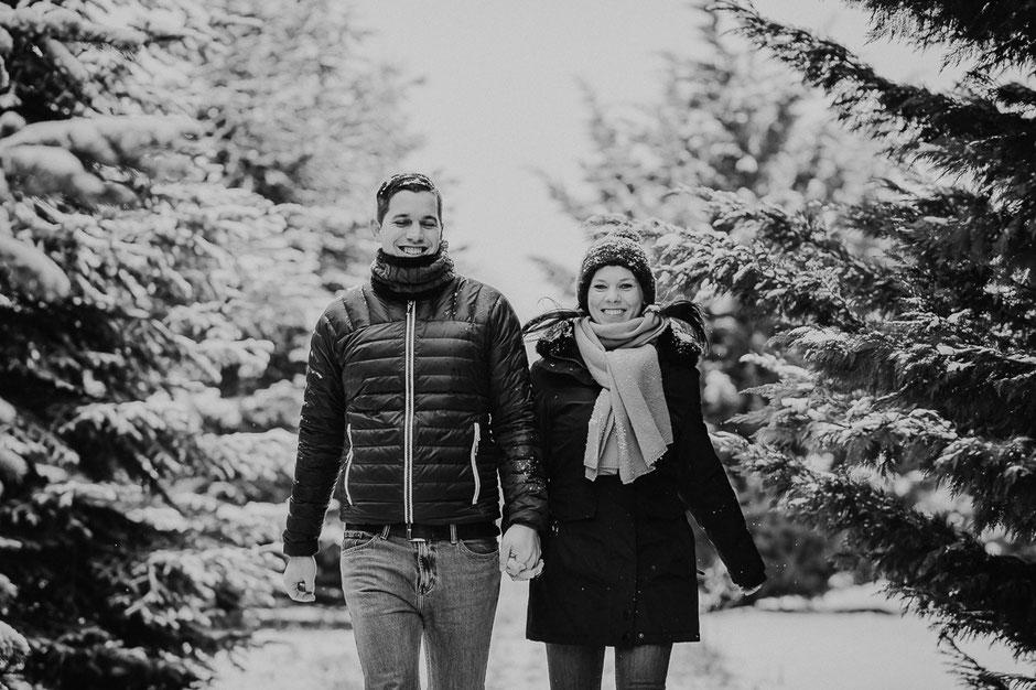 Paar geht Hand in Hand im Schnee in einem Wald bei Mainz