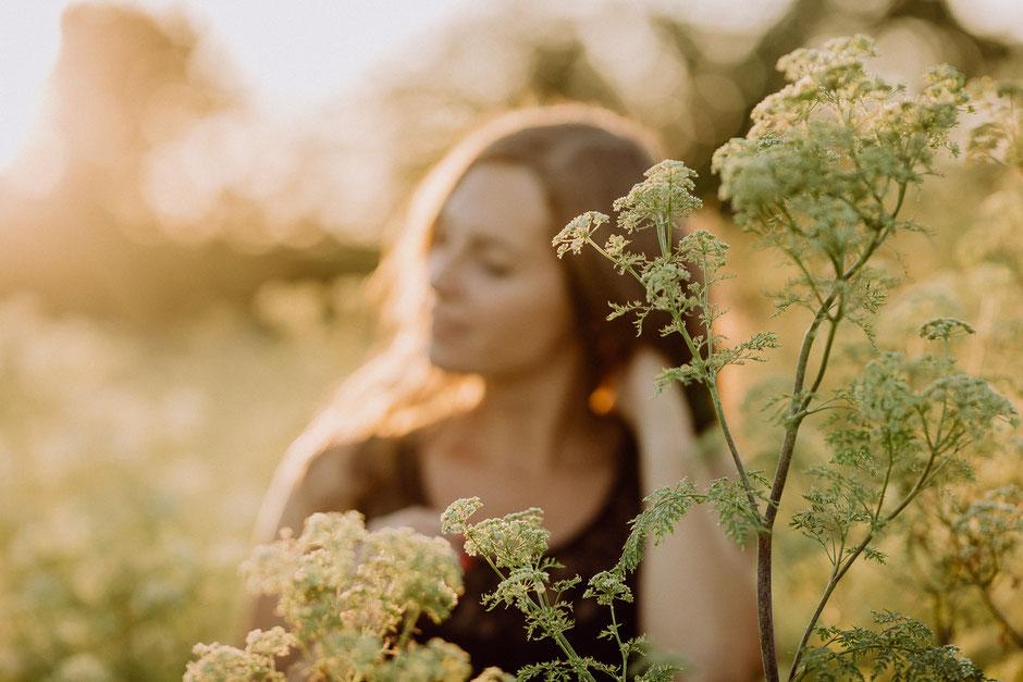 Silhouette einer Frau im Abendlicht auf einer Wiese