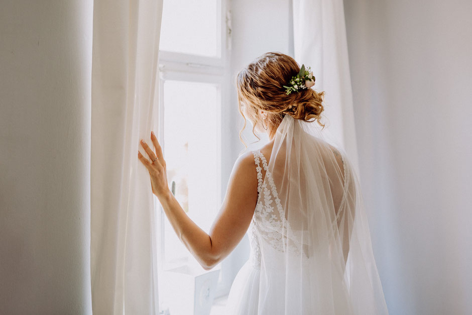 Braut schaut aus dem Fenster bei Getting-Ready in Rümmelsheim