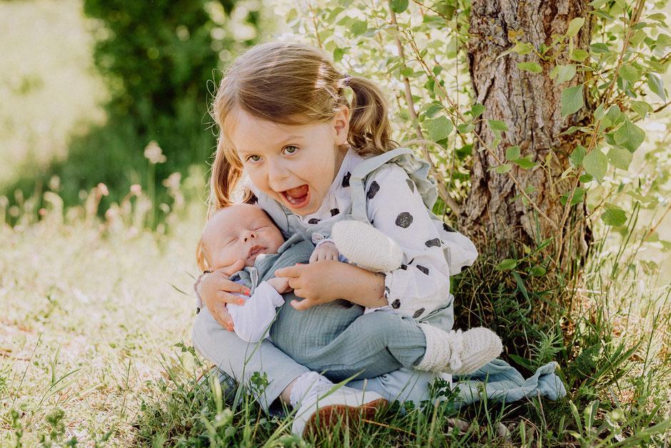 Große Schwester hält neugeborenes Baby auf dem Arm im Frühling
