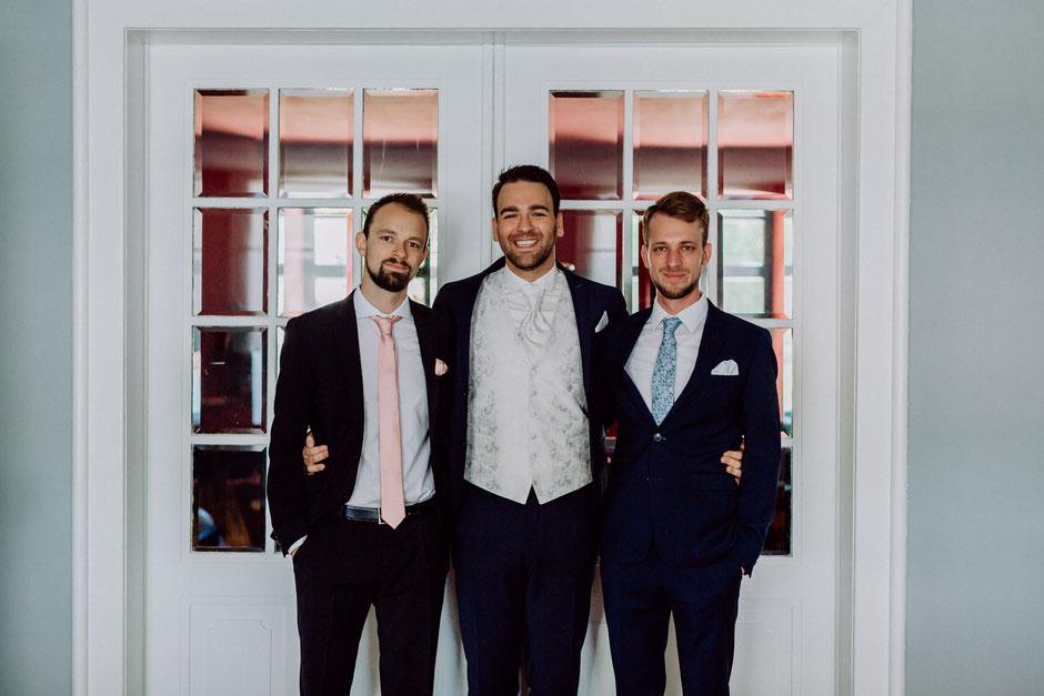 fröhlicher Bräutigam mit seinen Best Men vor der Trauung