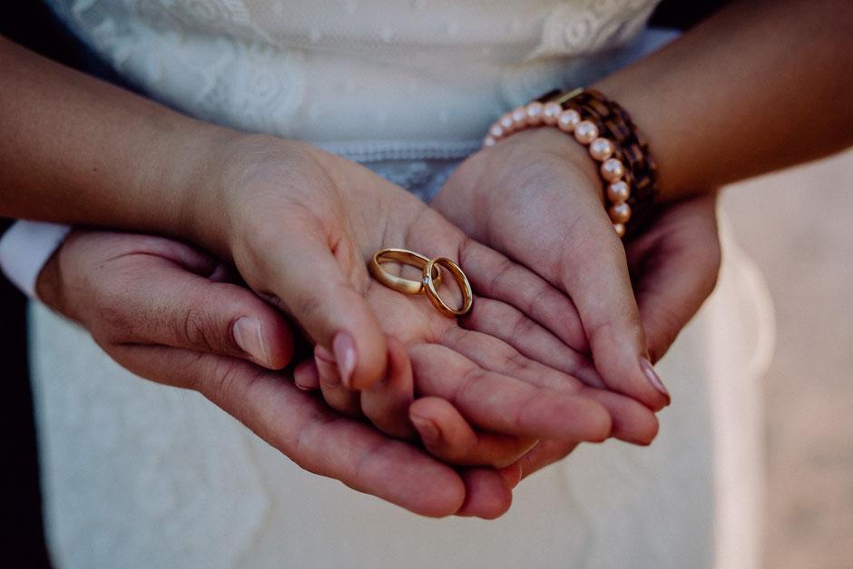 Goldene Eheringe in den Händen des Brautpaares