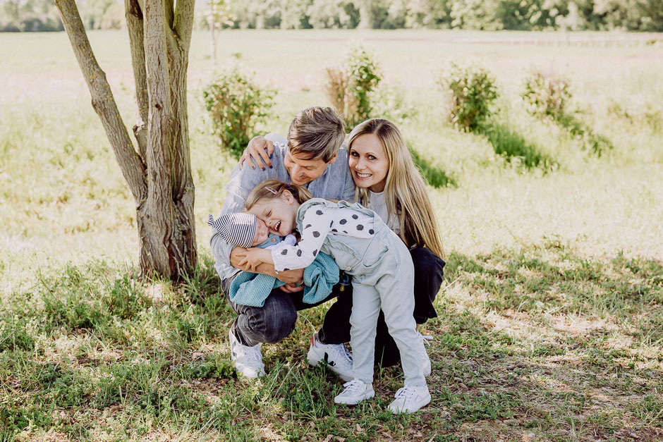 Familie kniet gemeinsam auf einer Wiese und umarmt den Bruder