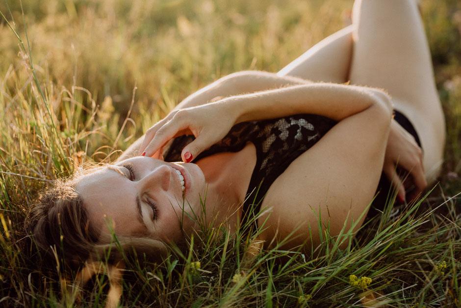 hübsche Frau liegt in schwarzer Wäsche auf einer Wiese