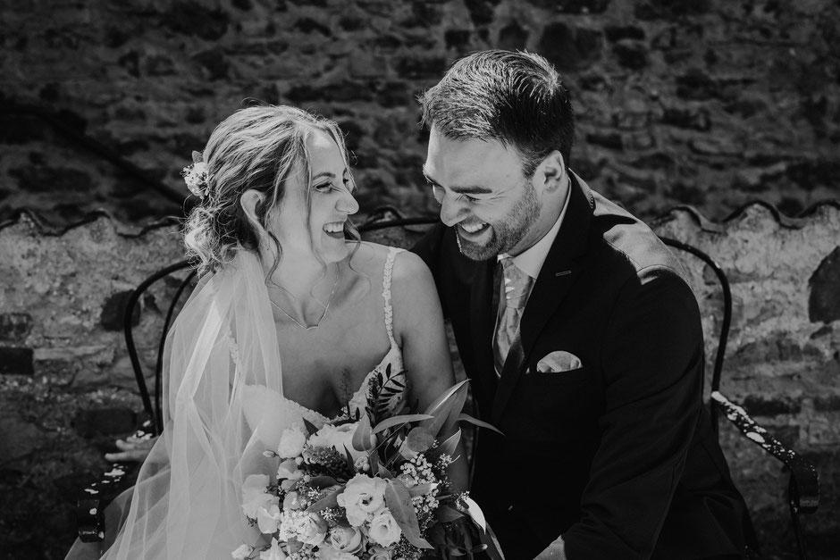 Braut und Bräutigam sitzen glücklich auf einer Bank vor der freien Trauung bei Mainz
