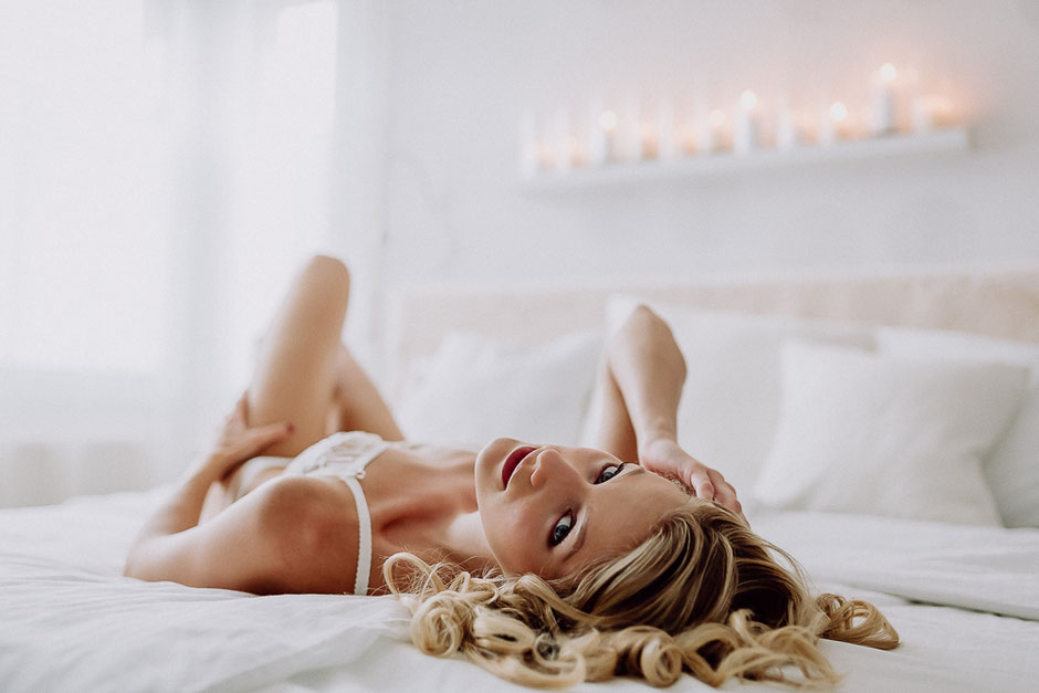 Braut liegt auf dem Rücken im Bett bei Boudoir Fotoshooting