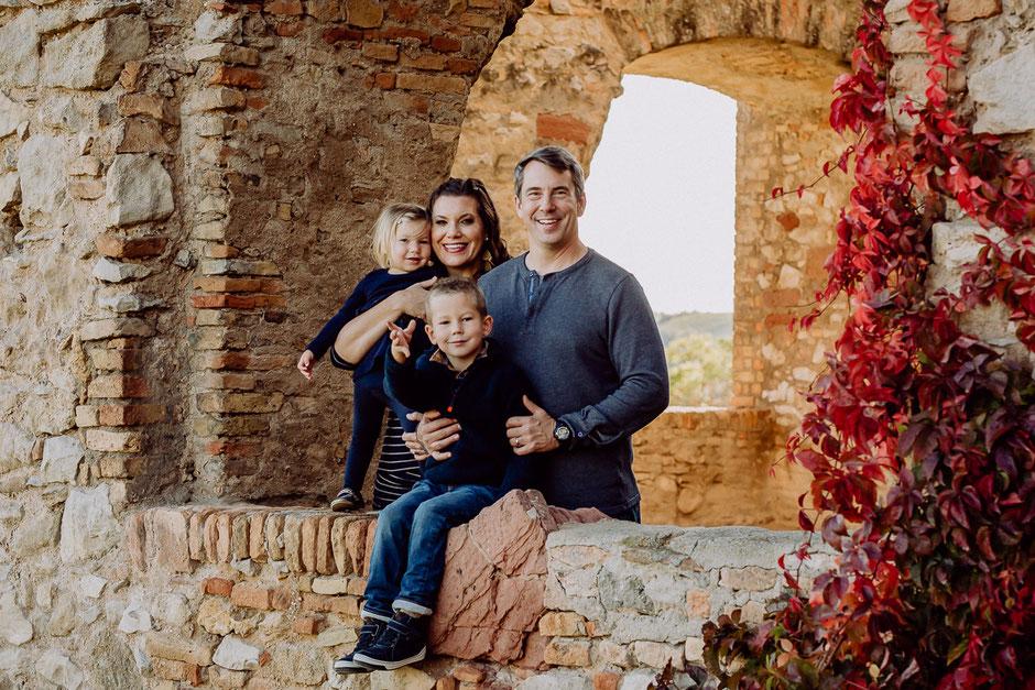 Familie schaut lächelnd in die Kamera aus einer Burgruine in Rheinland-Pfalz