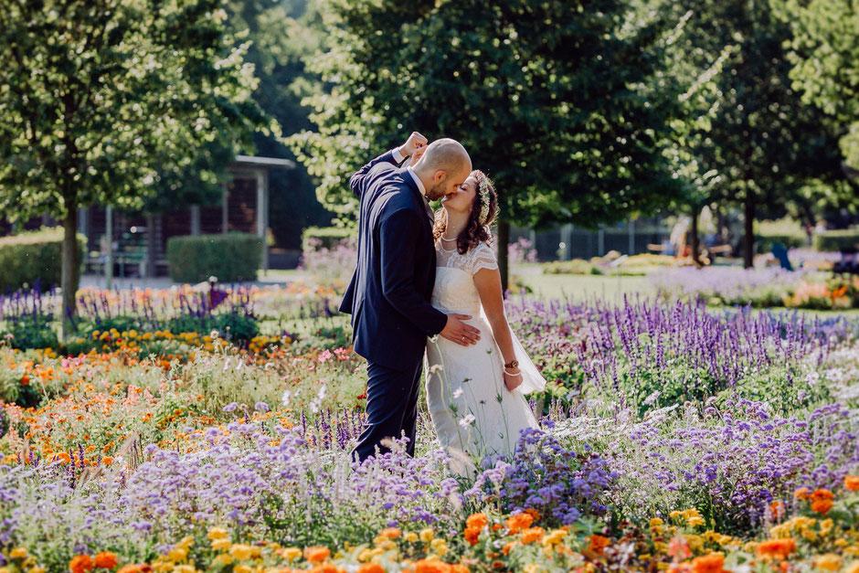 Fotoshooting mit glücklichem Brautpaar in einem Blumenmeer