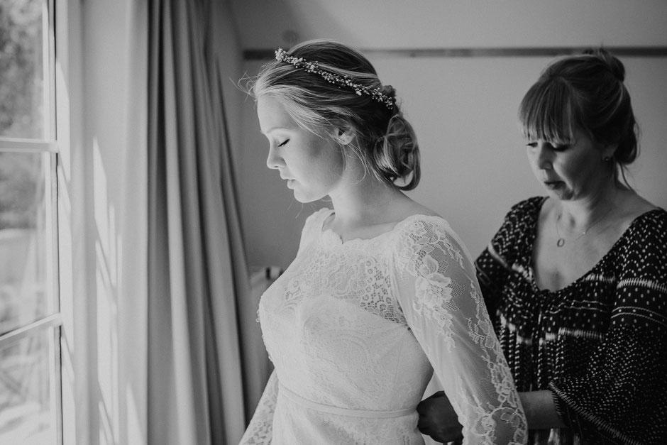 Brautmutter hilft Braut beim Ankleiden