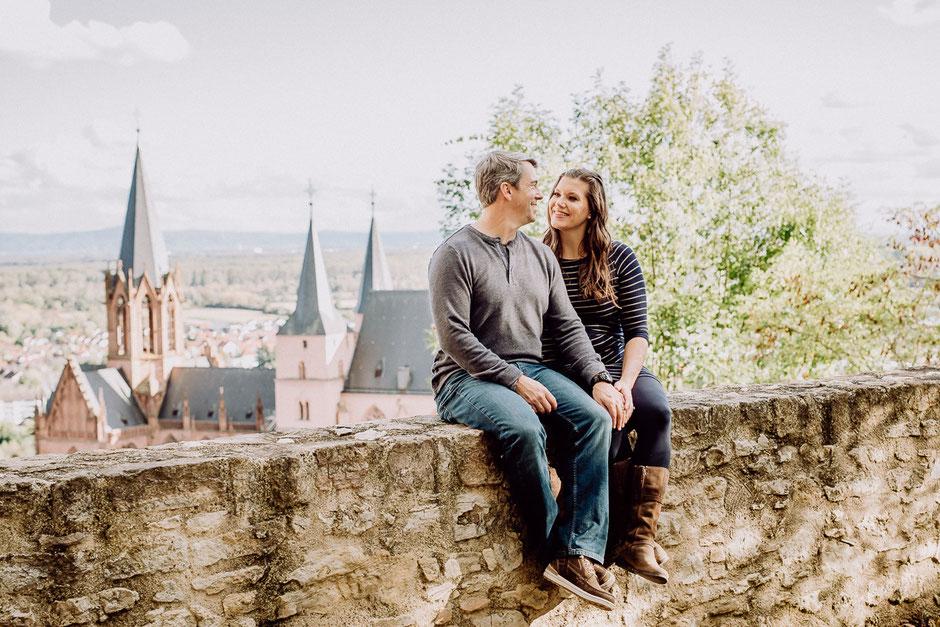 Ehepaar sitzt auf einer Mauer vor Katharinenkirche in Oppenheim