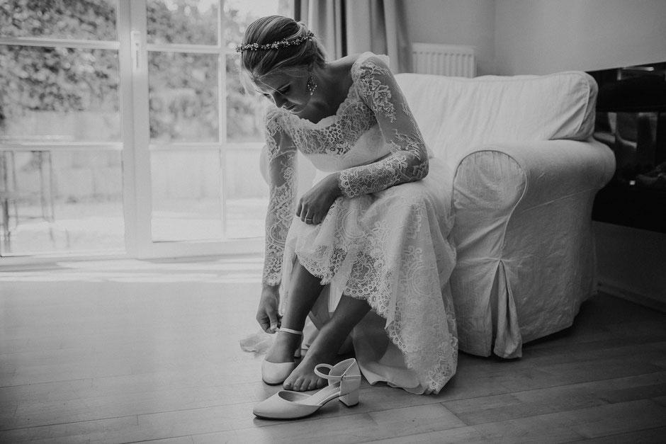 Braut zieht Brautschuhe an beim Getting Ready