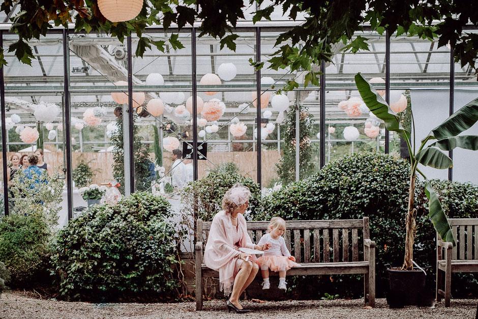 Brautmutter und Blumenkind sitzen vor Hochzeitslocation im Gewächshaus bei Hochzeit in Ladenburg