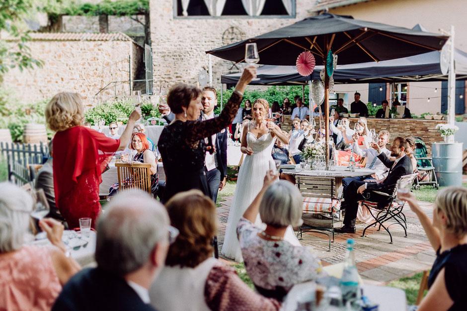 Familie hebt die Gläser und trinkt auf das Wohl des Brautpaares auf Schlossgut Diel