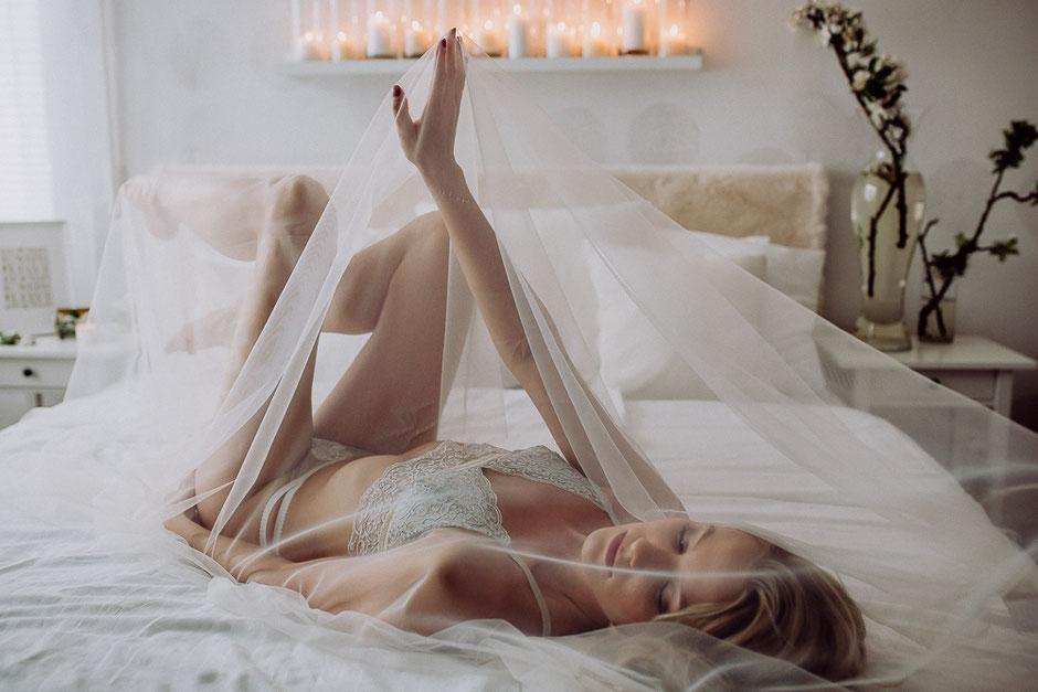 Braut liegt auf dem Bett mit Schleier bei Boudoir Fotoshooting in Rheinhessen