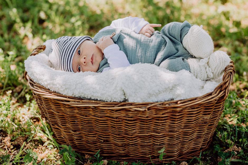 Baby liegt in einem Korb und schaut in die Kamera