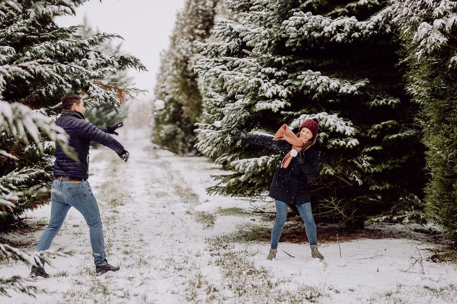 Mann wirft Schneeball auf lachende Freundin